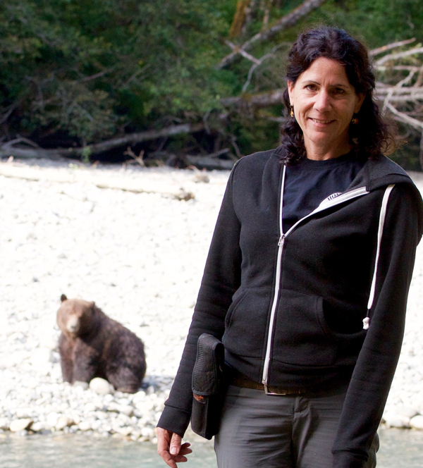 a woman standing next to a stream with a bear in the background